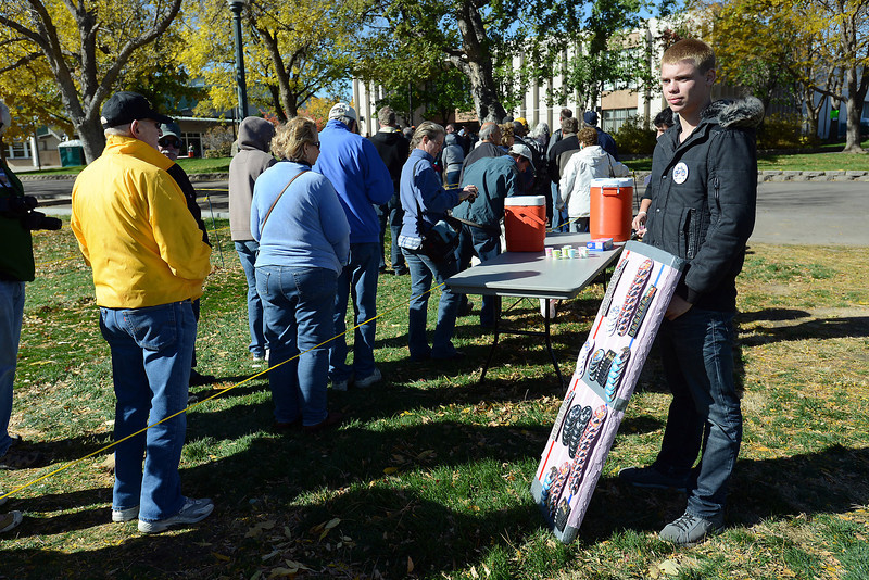 Denver resident Skylar Lucas, left, sells campaign buttons outside the Island Grove Regional Park's Exhibition Hall as people line up to go inside to listen to a speech by vice president Joe Biden during a campaign stop on Wednesday, Oct. 17, 2012 in Greeley, Colo.