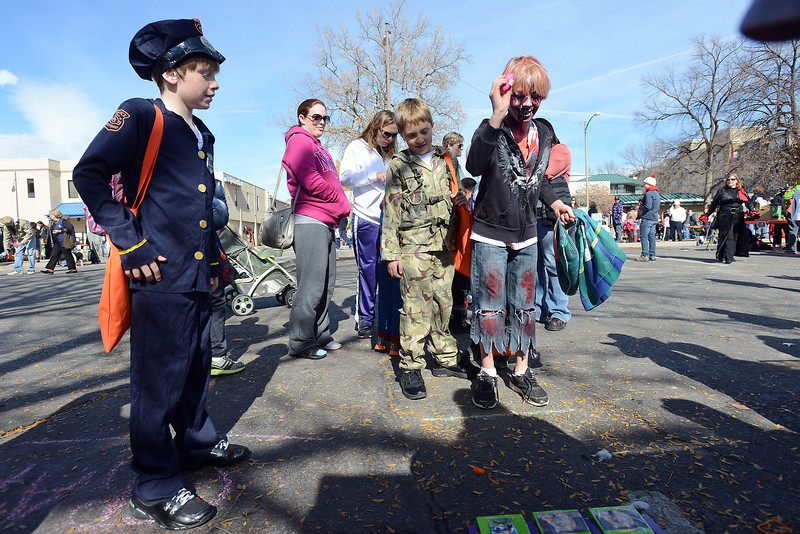 Mikey Berry, 10, left, looks on while Kaden Butler, 10, tries the bean bag toss game at the Fort Collins Cat Rescue booth during the Halloween Family Fun Festival on Saturday, Oct. 27, 2012 in downtown Loveland.