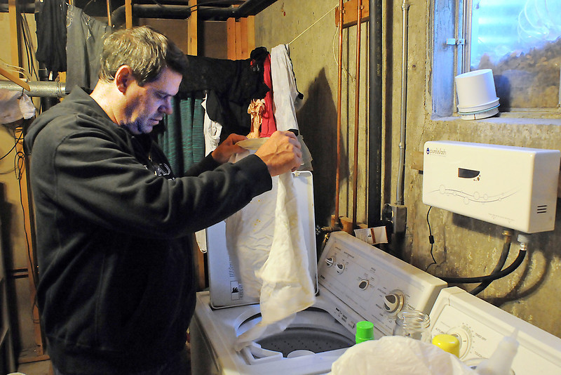 J. Day's Appliance store manager Danny Jackson, on his day off Thursday, drops some rags into the washing machine in his basement laundry room. His pureWash unit is mounted on the wall above the washer.