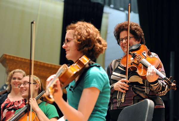 Barbara Hamilton, far right, and Judit McIntyre, far left, members of The Chamer Players, share a laugh with Loveland High School orchestra students Abigail Strand, 16, left, and Meaghan Ford, 16, right, during a workshop Tuesday at the school in Loveland. The Colorado Chamber Players came up from Denver to do a performance and workshop for the students.