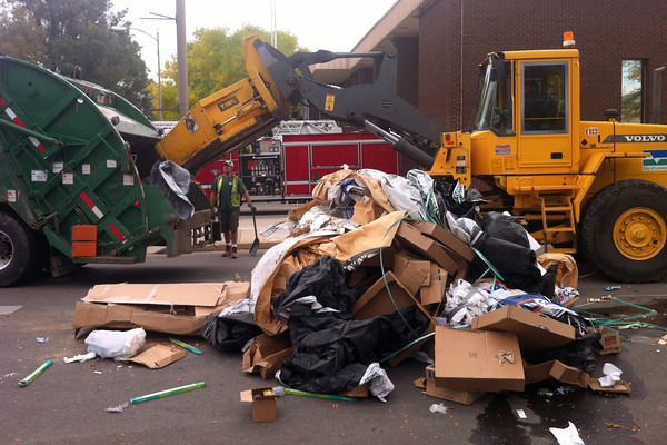 City workers dump trash into a Waste Management truck Wednesday afternoon after firefighters at Fire Station 1 in downtown Loveland, 410 E. Fifth St., extinguished a fire inside another trash truck.