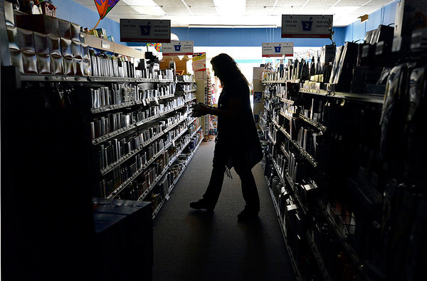 Debbie Schleiger, an employee at Berthoud Drug, tries to put products on the shelves in the dark Tuesday morning in Berthoud. Thousands of people were without power for about four hours in the Campion and Berthoud areas.
