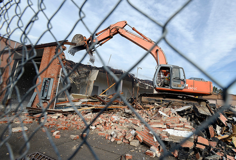 Driving over the rubble that once was the Leslie the Cleaner building, Bryon Dickey with CGRS uses an excavator to bite chunks out of a building next to the old Leslie the Cleaner building on the northwest corner of Lincoln Avenue and Third Street in downtown Loveland on Thursday afternoon. The buildings are being demolished in preparation for redevelopement.