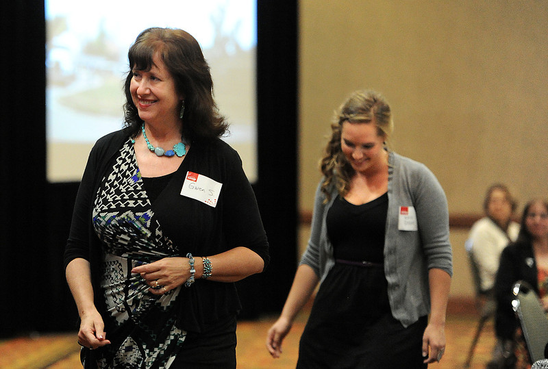Gwen Stephenson, left, executive director of Loveland Habitat for Humanity, and Kailey Staiano, right, a Loveland High School senior, who is participating in the Geometry in Construction program, make their way to the stage as they are announced as the winner of the Loveland Award during the Group Community Service Awards Thursday in Fort Collins.