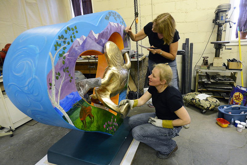 "Loveland-based artists Merrilee Cleveland, front, and Mary Benke work together as they put the finishing touches on a heart sculpture together on Wednesday, Oct. 3, 2012 in Cleveland's downtown studio. The sculpture is named ""Lover's Leap."""