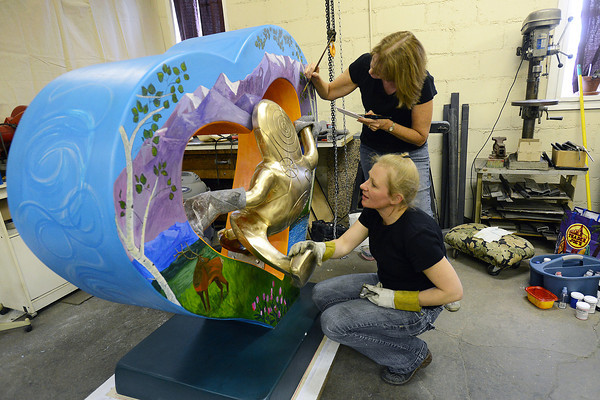 """Loveland-based artists Merrilee Cleveland, front, and Mary Benke work together as they put the finishing touches on a heart sculpture together on Wednesday, Oct. 3, 2012 in Cleveland's downtown studio. The sculpture is named """"Lover's Leap."""""""