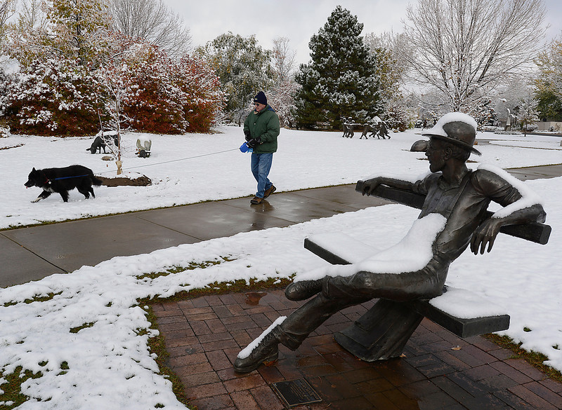 "Sculptures are covered in snow as Duane Huggins of Loveland walks his dog Mandy, an 11 year-old border collie, through Benson Park Sculpture Garden on Thursday morning in Loveland. Talking about Mandy in the snow Huggins said "" She loves it. She lays in it."""