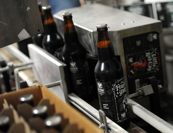 Bottles of Grimm Brothers The Fearless Youth beer are moved on a conveyor belt after labels are attached.
