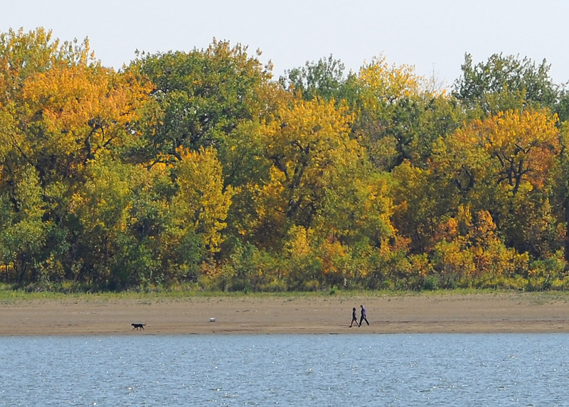 Taking advantage of the warm temeratures, folks walk their dog past trees turning fall colors at Lonetree Reservoir Monday west of Loveland.