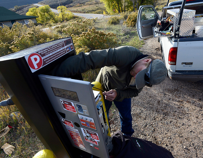 Steve McCorkel, a Larimer County maintenance technician, works to install a new automated pay station Monday near Carter Lake west of Loveland. Larimer County has purchased pay stations for all of its parks and open spaces after a successful year-long test at Horsetooth Mountain Park.