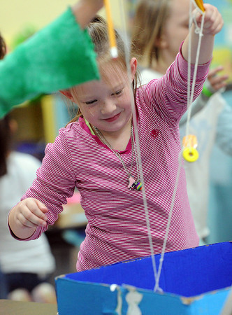 """Allison Morrison, 7, a second-grader at Edmondson Elementary School, plays the """"Fishing Pond"""" cardboard game Friday at school during the Cardboard Challenge/Global Day of Play."""