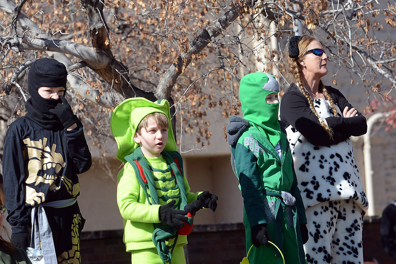 Dylan Fitzgerald, 10, left, Dakota Fitzgerald, 7, Corbyn Williams, 8, and Sabina Fitzgerald watch the costume contest while waiting to compete during the Halloween Family Fun Festival on Saturday, Oct. 27, 2012 in downtown Loveland.
