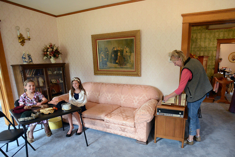 Berthoud Historical Society volunteers Aynsleigh Wood, 8, left, and Evelyn Wood, 11, sit near a table with period hats on display while Dacono resident Karen Reid looks through books from the early 1900's during the Women and Daughters on the Homefront During World War II event on Saturday, Oct. 20, 2012 at the McCarty-Fickel Home Museum at 645 Seventh St. in Berthoud.