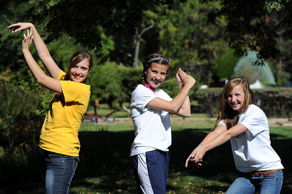 Lillian Koso, 14, left, Gianna Tricarico, 13, center, and Allie Woodward, 13, strike a sports pose for the camera Monday in Loveland.