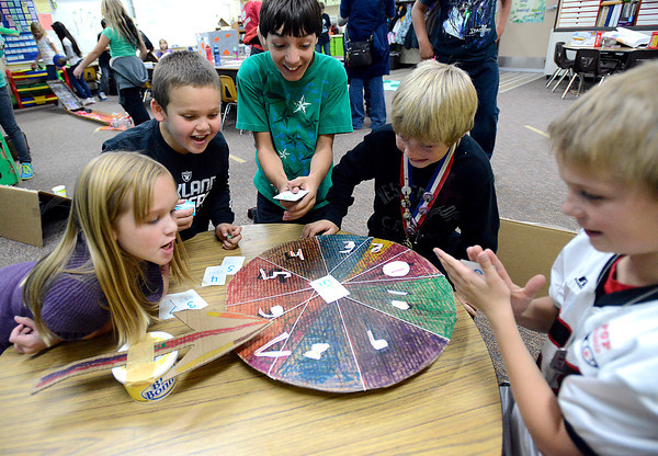 """Edmondson Elementary School students play a game made of cardboard called """"Wheel of Fortune"""" Friday at the schol in Loveland. The students created cardboard games and made the rounds playiong all the games as part of their Cardboard Challenge/Global Day of Play. From left they are Samantha Clymer, 9, Satchel Foren, 10, Noah Bryant, 10, Alex Modak, 9, and Cody Weimer, 11."""