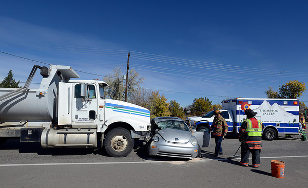 Loveland Fire and Rescue firefighters work the scene of a three-car accident where a VW Bug crashed into a dump truck Monday morning in the 3500 block of West U.S. 34, a little bit east of the La Quinta Inn in Loveland. The driver of the bug escaped serious injury and no one was trasported to the hospital after the accident.