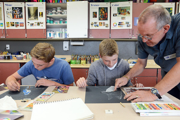 "Resurrection Christian School art teacher Mark Silvers, right, assists Luke Wagner, 16, middle, and Jacob Wapnick, 16, as they work on oil pastel drawings during 2-D art class in preparation for the upcoming ""Art for Water"" show and fundraiser auction."