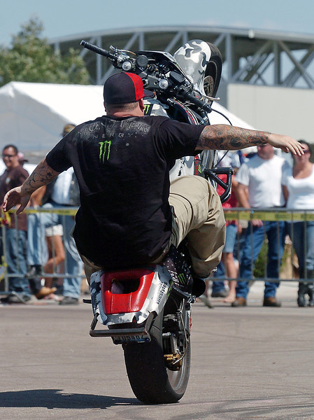 Suicical Lifestyles stunt rider Jack Polzin rides a wheelie with no hands while performing Sunday for attendees to the Thunder in the Rockies motorcycle rally.
