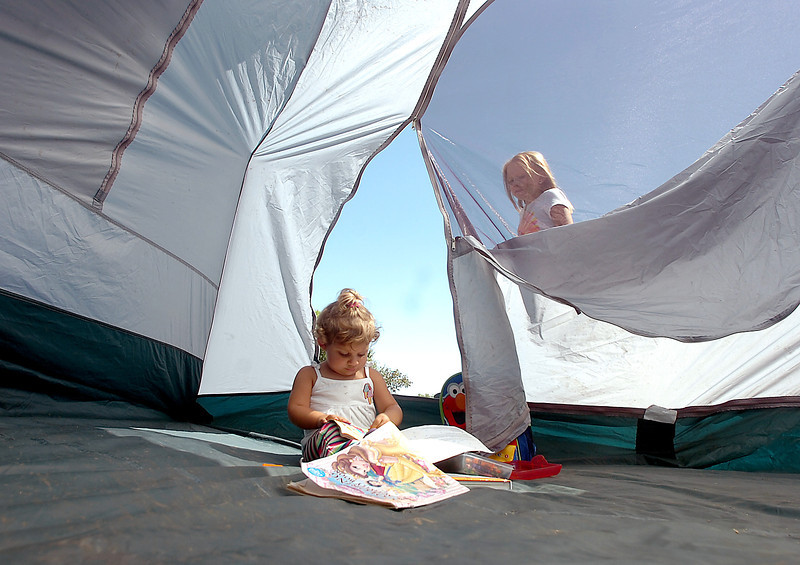 Katrina Book of Loveland, 2, colors while she sits in her family tent as her cousin Baylee Adent, 9, looks through the window Friday at Boyd Lake State Park in Loveland. Their families were setting up camp for a long Labor Day weekend.