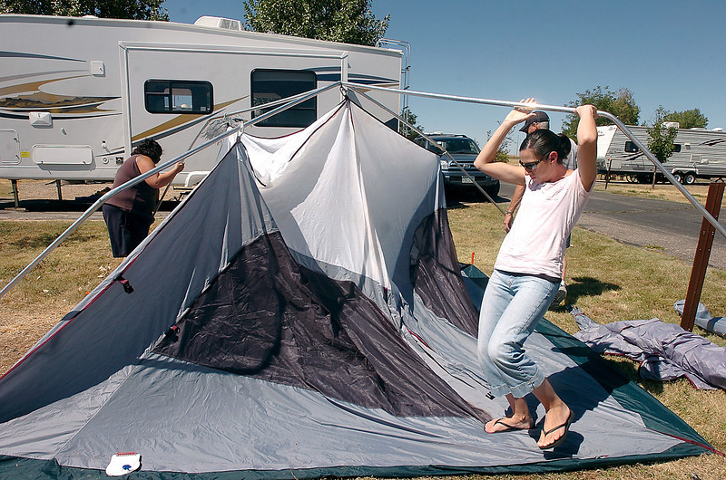 Sara Adent of Loveland, right, ducks under a tent pole while helping her cousin Gina Book, left, and her dan Chris Klaas, behind her, put up the Book's tent Friday at Boyd Lake State Park in Loveland.