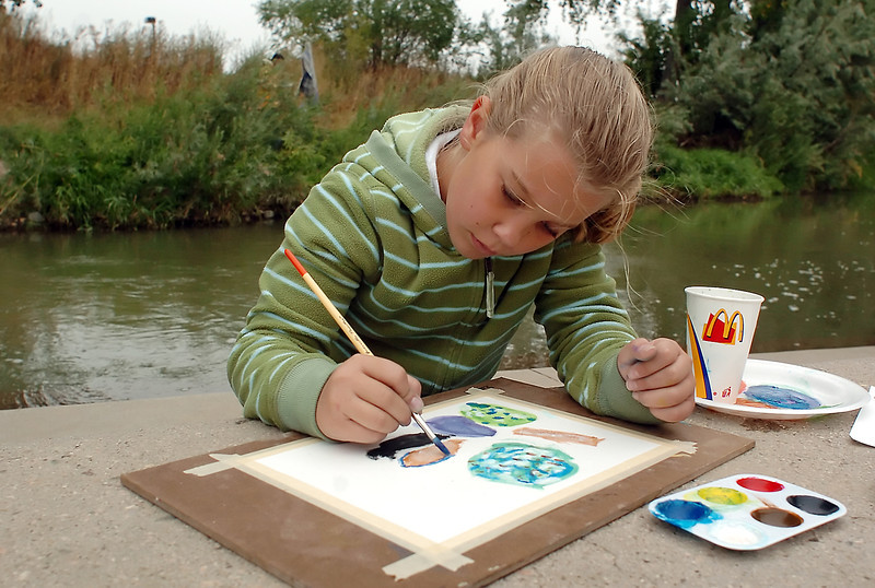 Kelsey McComas, 10, works on a painting Saturday morning along the Big Thompson River at Fairground Park during a class for Plein Air art students from the Thompson School District.