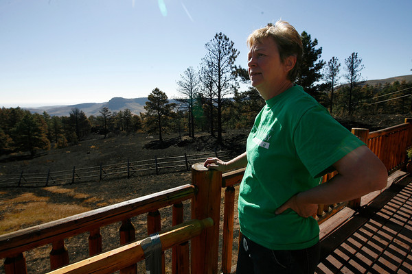 Jan Leach stands on the balcony of her home and shows how close the flames came to her house Sunday.  Leach had about a half hour to spray her house and gather belongings before evacuating last Sunday. (Photo by Gabriel Christus)
