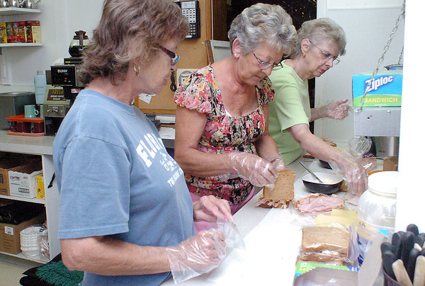 Volunteers, from left, Marilyn Epp, Shirley Brunelli and Roberta Steinwachs assemble sandwiches Wednesday afternoon in the kitchen at the Loveland Elks Club, 103 E. Fourth St., for wildland firefighters who were resting there after working at the Reservoir Road fire.
