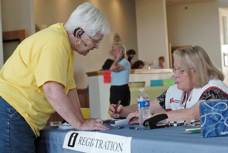 American Red Cross worker Sandy Hill, left, assists Terri Washburn at the evacuation center set up at The Church at Loveland, 3835 SW 14th St. on Sunday where individuals affected by the Reservoir Road fire west of Loveland. Washburn is from Anna, Tex., and was seeking information for her sister, who lives in the fire evacuation area, about where displaced pets and animals were being taken.