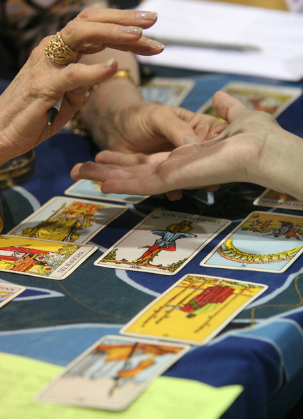 A client has her tarot cards read by Sandra-Ka, clairvoyant channel, tarot reader, at a Holistic Fair on Sept. 26 at The Ranch in Loveland. (Heather A. Longway/ The Reporter-Herald)
