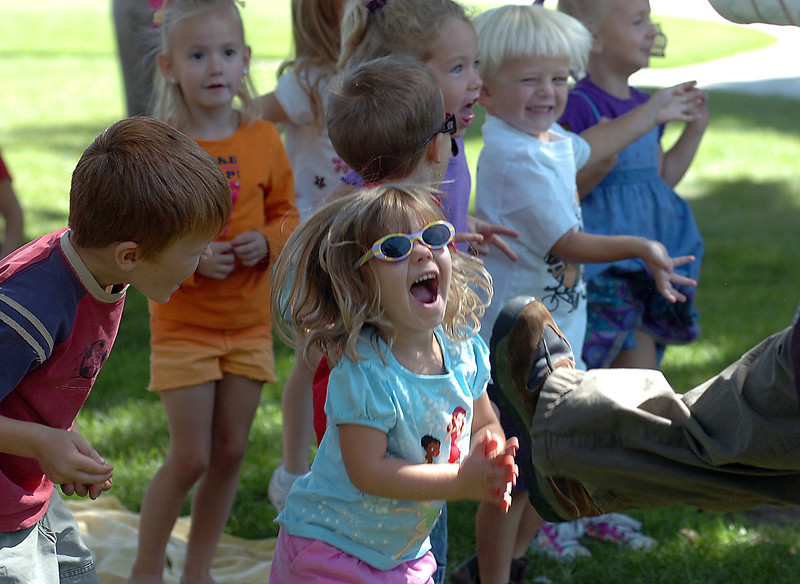 Anna Tobey of Loveland, 3, giggles as she and classmates from Loveland Preschool pretend to be transported to the dinosaur times Friday during a presentation by the Dinosaur Lady, Connie Burkhart, at North Lake Park. The preschool celebrated its 43rd birthday at the park Friday.