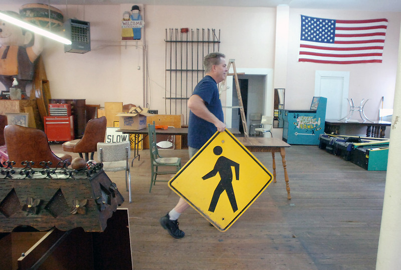 Peder Thorstensen carries a sign while arranging items Monday at his soon-to-be-opened busniess, Rawhide Auctions, located at 349 Massachusetts Ave. in downtown Berthoud. The space will be used on Friday and Saturday nights to serve as the Berthoud Youth Center beginning in approximately two weeks.