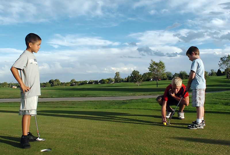 Marcelo Espinoza Diaz, 8, left, and Wesley Howard, 7, right, are tutored by Loveland High School golfer Cole Bundy, 14, on the practice green at Cattail Creek Golf Course on Monday during the the Boys and Girls Invite sponsored by the Loveland High School boys golf team.