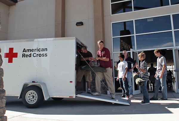 Volunteers from The Church at Loveland, located at 3835 SW 14th St., help unload supplies from an American Red Cross first-response trailer Sunday at the church where an evacuation center was set up for people displaced by the Reservoir Road fire. From left are Jeremiah Mejia, Thomas Nettersheim, Gabe Mejia, 15, Carl Sheldon, Elijah Harold, 14, and Peter Harold, 16. The trailer had 50 cots, 100 blankets, bottles of water and other supplies to get the shelter started.
