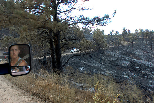 Resident Amanda Mitchell is refelcted in the rearview mirror of her truck as she gets a first look at the devastation from the Reservoir Road fire west of Loveland. She and her husband Josh were among the first group of residents allowed to go back home for a short time to gather belongings and pets.