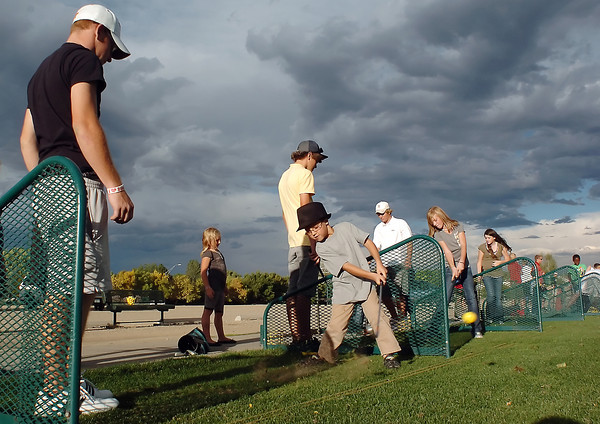 Six-year-old Marshall Gray, center, hits a shot under the watchful eye of Loveland High School golfer Tanner Swayne, left, at the Cattail Creek driving range Monday during the Boys and Girls Invite sponsored by the Loveland High School boys golf team. A total of 19 kids from the club were given instruction by the high school golfers during the annual event.