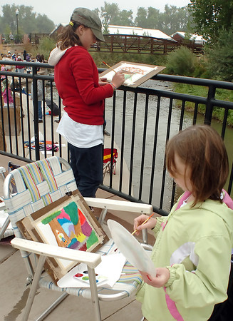 Loveland residents Kelsey Porter, 9, right, and Tori Miller, 10, work on paintings Saturday at Fairgrounds Park during a class for art students from the Thompson Valley School District.