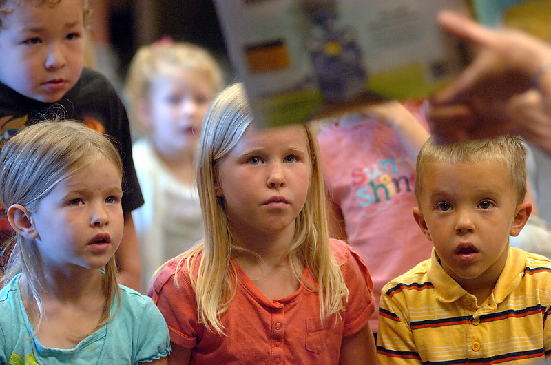 Children listen to a story about dinosaurs and trains Wednesday during storytime at the Loveland Public Library. Clockwise from left they are James McDonough, 4, Ellie Gunderson, 5, Anna Gunderson, 7, and Jed Gunderson, 4.