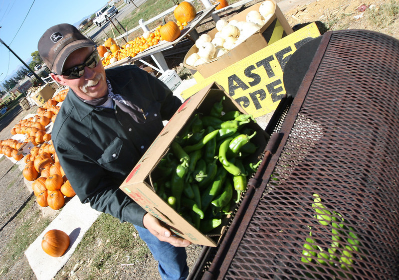 Jake Hill, son of the owner of Jake's Farm, roasts chili peppers at the farm on Sept. 26 near Eisenhower Blvd. and Boyd Lake Avenue in Loveland. (Heather A. Longway/ The Reporter-Herald)