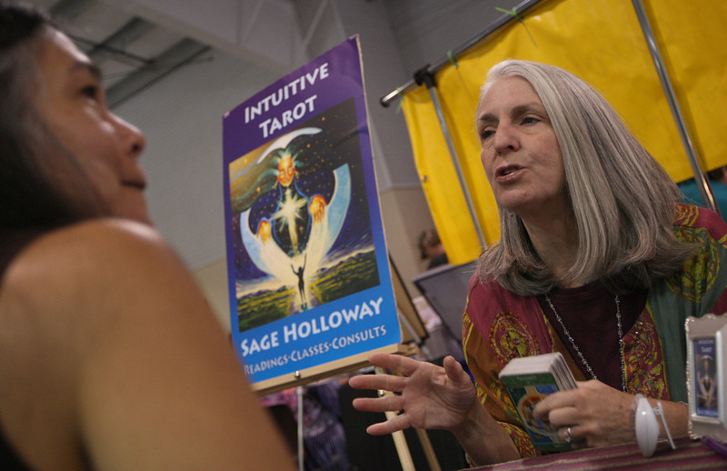Sage Holloway (right), intuitive counselor, reads Renee Lapenia-Shields' tarot cards at a Holistic Fair on Sept. 26 at The Ranch in Loveland. (Heather A. Longway/ The Reporter-Herald)