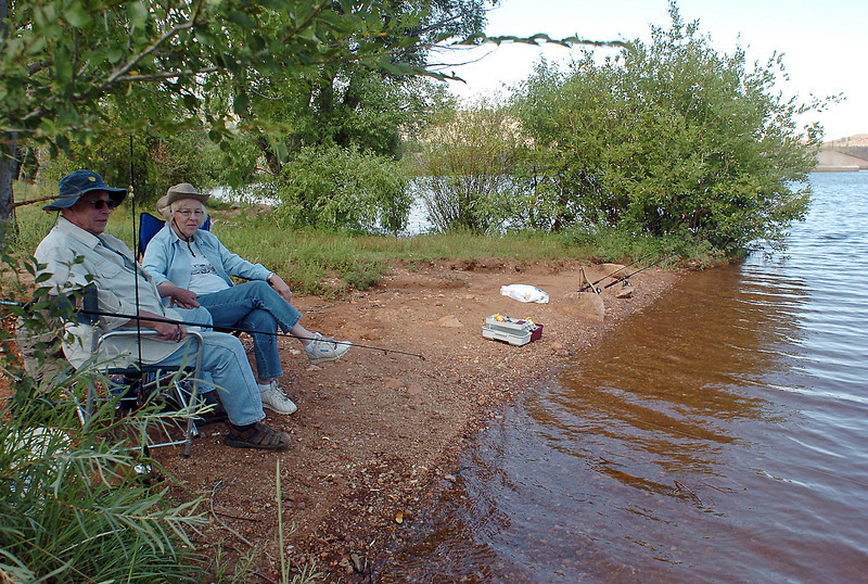 Jay Nunn, left, and Eileen Treichel sit along the shore at Flatiron Reservoir southwest of Loveland while fishing together Tuesday afternoon.