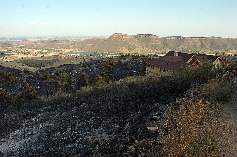 Land surrounding a home on Turkey Walk Trail is blackened from the Reservoir Road fire west of Loveland.