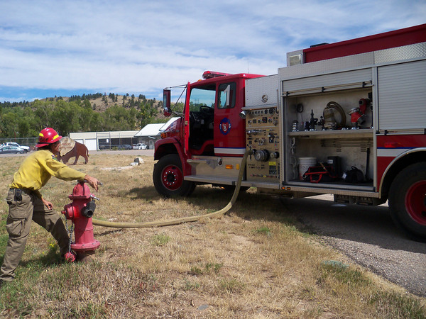 Big Thompson Canyon volunteer firefighter Delbert Nussbaum fills a Loveland fire tanker with water from a hydrant at the Bison VisitorÕs Center at Carter Lake. He made several trips with the 1,800-gallon tanker as the fire grew from three to 600 acres by late Sunday.