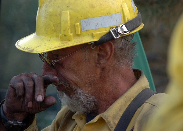With hands blackened from fighting the Reservoir Road fire, firefighter Loyd Holliman with Long Canyon Fire takes a break Wednesday evening.