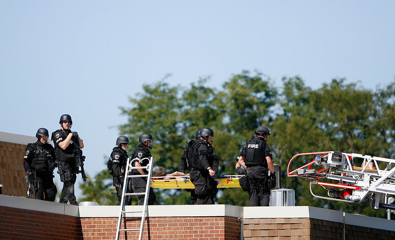 Special Weapons And Tactics units from the Loveland Police and Larimer County Sheriffs office cart a suspect off the roof of Laurene Edmonson Elementary School after a standoff Sunday at in Loveland. (Photo by Gabriel Christus)