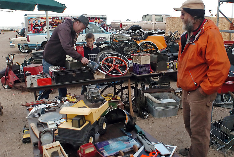 Steve Hartz, left, and Stevie Hartz, 8, of Ovid, Colo., look at items on display at the booth of Fort Collins resident Lannie Pickering, right, on Saturday at The Ranch during the Poudre Valley Antique Auto Swap Meet. The swap meet continues today from 8 a.m. to 3 p.m.