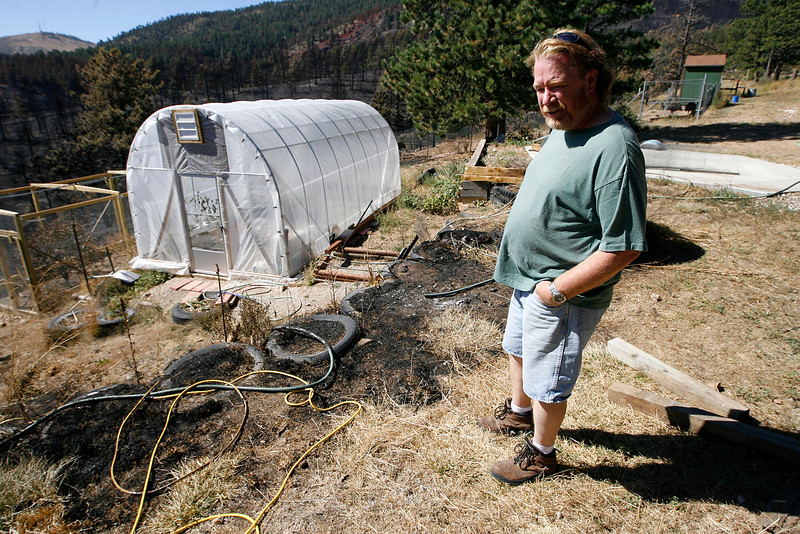 Tom Theilgaard shows the his damaged property from the fire on Sunday at his home. The only real damage was a garden hose and an extension cord. (Photo by Gabriel Christus)