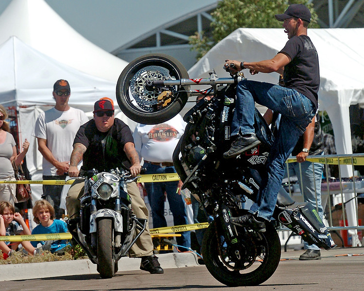 Suicical Lifestyles stunt rider Joe Trimbath, right, does a trick while teammate Jack Polzin and others watch Sunday at the vendor booth area of the Thunder in the Rockies motorcycle rally.
