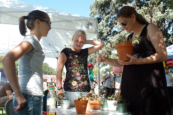 Valerie Peek, 12, left, and Alia Jackson, 12, assist Emily Waser as she picks out a free plant at the girls' booth Saturday during Peace in the Park at Foote Lagoon.