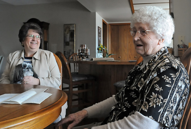 Loveland resident Tillie Edwards, right, shares a laugh with her daughter, Nancy Margheim, left, who is holding their dog, Maggie, while reminiscing together Thursday afternoon. Tillie turns 100 years old today and a birthday party for her is scheduled for Sunday from 2 p.m. to 4 p.m. at Bethel Lutheran Church, 328 Walnut St., in Windsor.