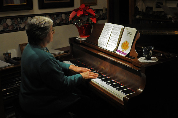 Judy Johnson plays the piano as her husband and children sing along. Johnson and her husband Murrell met in a music class at college. Their children, who were surrounded by music growing up, all play piano and other instruments.